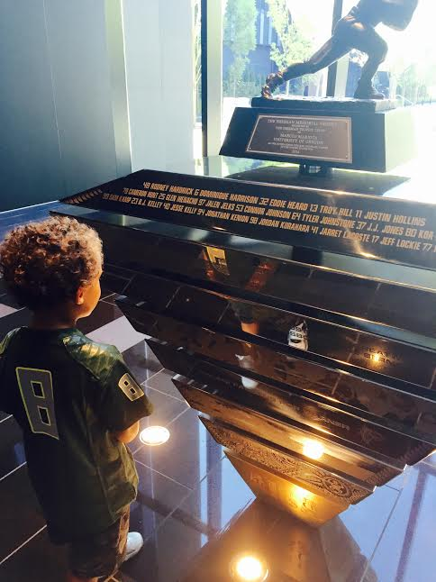 Eugene resident, Jordan Giles, looks at his reflection in Permanent Heisman Trophy Display honoring Marcus Mariota